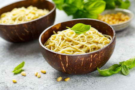 Delicious pasta with pesto sauce served in bowls of coconut Reklamní fotografie