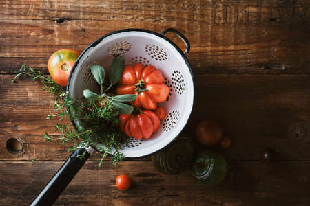 Farm tomatoes and herbs in a colander Reklamní fotografie