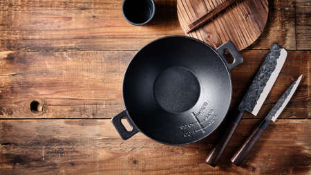 Set of dishes for Asian cuisine, small cast iron wok, Japanese knives on a wooden background.