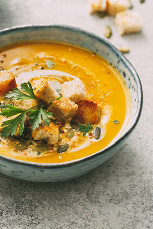 Pumpkin soup in a bowl garnished with pumpkin seed and croutons. Reklamní fotografie