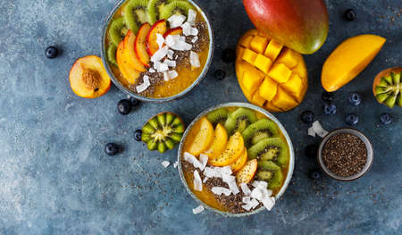 Healthy Mango Smoothie with chia seeds, coconut flakes, kiwi and blueberries, copy space