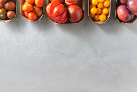 Different types of tomatoes in little trays with copy space over shabby grey background.