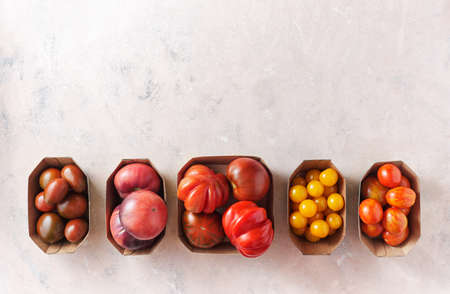 Different types of tomatoes in paper packaging on a shabby pink background, top view. Reklamní fotografie