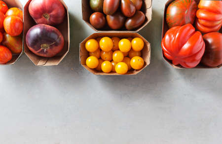 Different kinds of organic tomatoes in paper packaging on a shabby background with copy space.