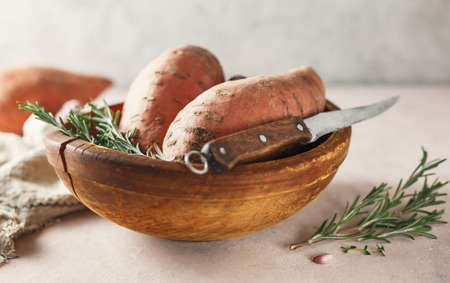 Sweet potatoes in a large wooden bowl with rosemary, close up.
