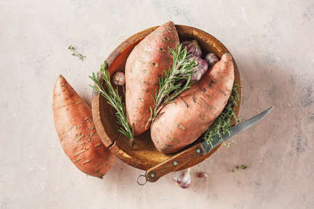 Sweet potatoes in a large wooden bowl with rosemary and garlic.
