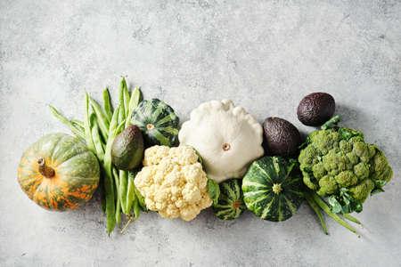 Brócoli, coliflor, judías verdes, calabaza y otros frescos sobre un fondo gris.