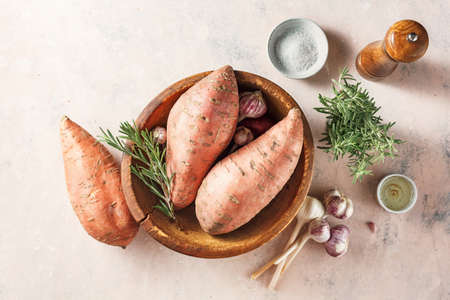 Sweet potatoes in a large wooden bowl with rosemary and garlic, top view. Reklamní fotografie