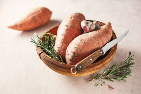 Organic sweet potatoes in a wooden bowl. Harvest season. Selective focus. Reklamní fotografie