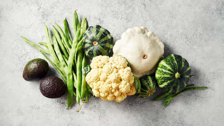 Broccoli, cauliflower, green beans, squash, and other fresh vegetables from the garden on a grey background.