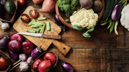 Fresh vegetables, tomatoes, broccoli, eggplant, onions on a wooden surface. Healthy food cooking background, copy space. Reklamní fotografie