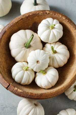 White little pumpkins in a wooden bowl, close-up. Holiday decorations.