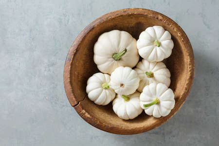 White little pumpkins in a wooden bowl, for holiday decorations, top view. Autumn background with copy space. Reklamní fotografie