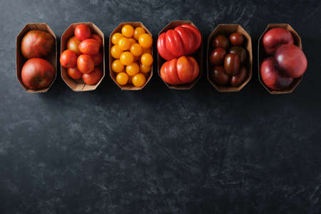 Different types of tomatoes in paper packaging on a dark background, top view. Top view.