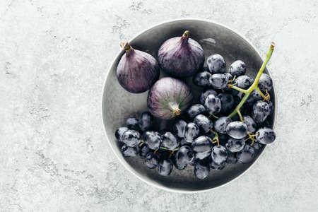 Organic whole figs and grapes in a bowl. Top view, copy space.