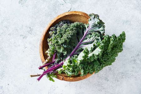 Green and purple Kale leaves in a wooden bowl, top view. Selective focus.