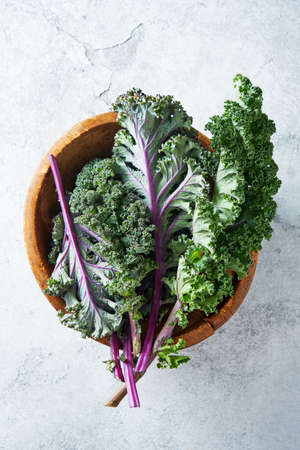 Green and purple Kale leaves in a wooden bowl, top view. Healthy fresh vegetables.