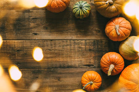 Different pumpkins on a wooden surface with bokeh lights. Festive background for autumn holidays. Top view.