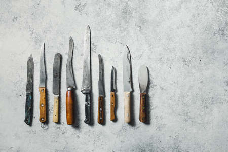Old knifes on a grey background. Top view, space for text. Reklamní fotografie - 130738422