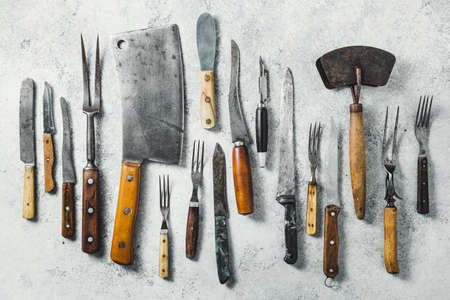 Vintage utensils, meat cleaver, forks and knifes on a light textured background. Top view.