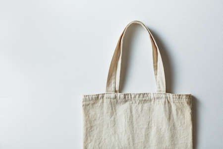 Cotton eco bag on a gray background, copy space, top view.