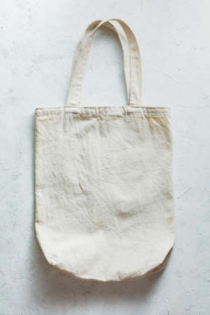 Modern canvas shopping bag on light background. Top view, copy space.