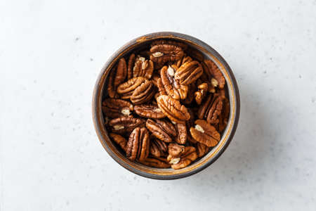 Peeled pecan halves in a bowl, on white background. Close up,Top view.