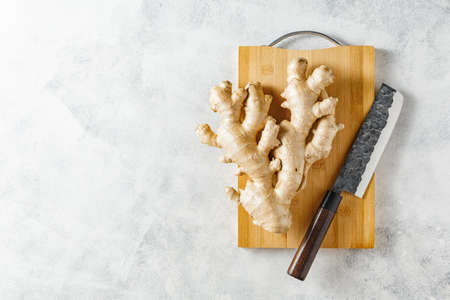 Fresh ginger root on a cutting board, copy space, top view. Imagens