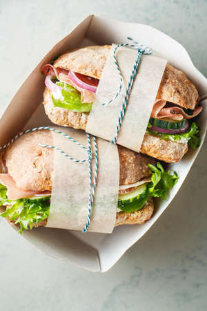 Whole wheat bread sandwiches with ham with ham, cucumbers, lettuce and onions. Stock Photo