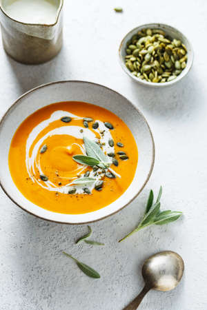 Creamy pumpkin soup with pumpkin seed and fresh herbs. Stock fotó