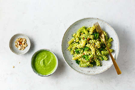 Fusilli with green pesto sauce, broccoli and cashew nuts. Top view.