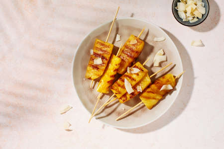 Grilled pineapple wedges on wooden skewers on a plate, top view. Hard light.