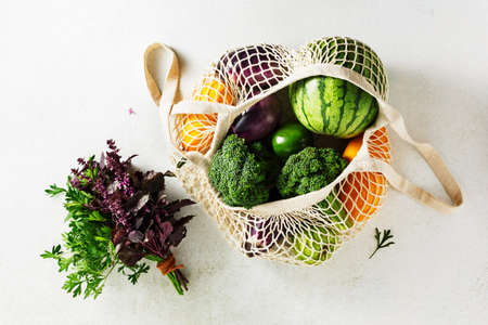 Reusable shopping bags with vegetables, zucchini, eggplant, watermelon. Top view. Sustainable lifestyle concept.