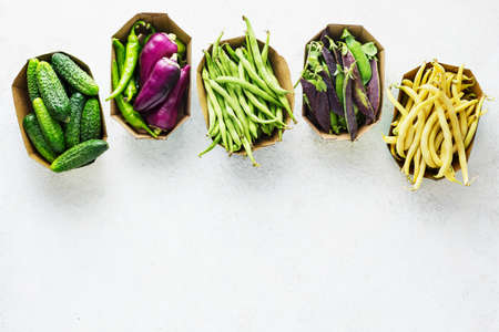 Green and purple organic vegetables in paper packaging, cucumbers, beans, peas, bell peppers. Food background with copy space.