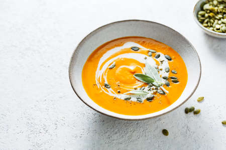 Spicy vegetable soup with pumpkin seed and fresh herbs. Selective focus.