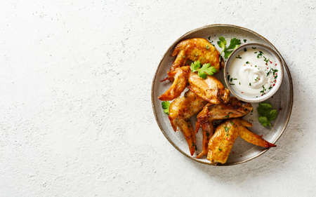 Baked chicken wings with herbs and dip.