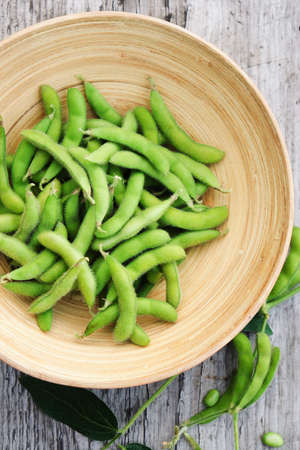 Organic green soybeans in a bowl on a rustic tabletop. Top view. Stock fotó