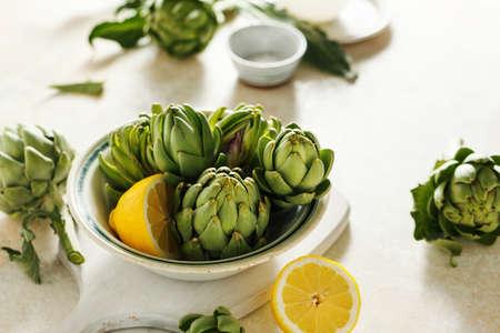 Raw artichokes in a bowl and lemons. Stock fotó