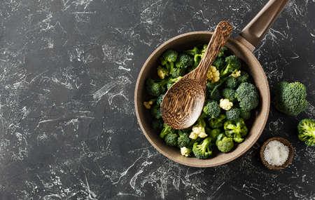 Fresh broccoli in a pan on a dark background.