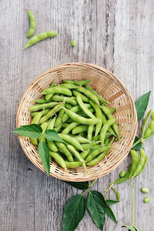 Edamame green pods in a bowl on a wooden table. Top view. Stock fotó