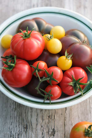 Various colorful tomatoes in a bowl on the old wooden table. Selective focus.