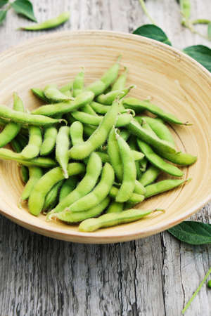 Raw green soybeans in a bowl on a rustic table. Selective focus.