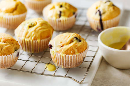 Homemade muffins with blueberries and lemon frosting, close up. Stock fotó - 156155996