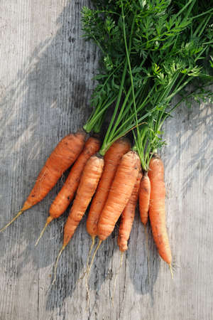 Bunch of organic carrots on a wooden surface. Stock fotó - 156474062