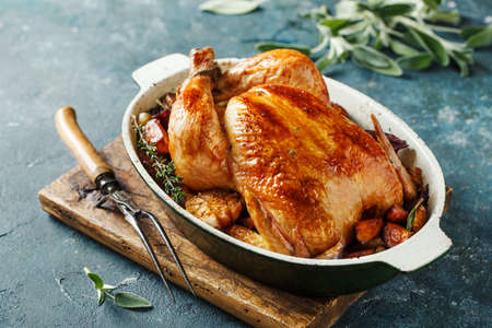 Whole roasted chicken with vegetables on wooden cutting board Stock fotó - 156528547