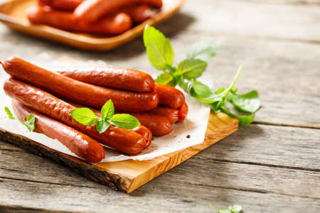 Smoked sausages with spices and aromatic herbs on a cutting board, wooden background.