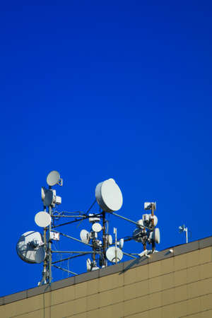 Cellular aerials against the vivid blue sky. Microwave transmission tower