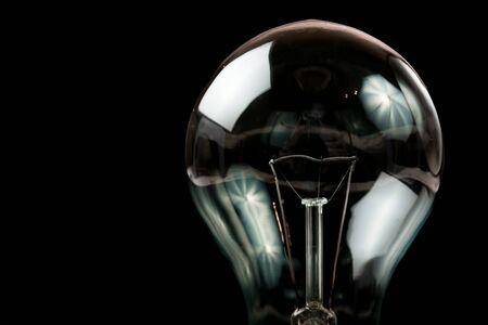 Glühbirne auf schwarzem Hintergrund Standard-Bild