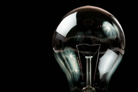 Incandescent light bulb on a black background