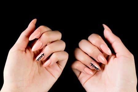 Manicured girl hands on a black background. Pink coral nails